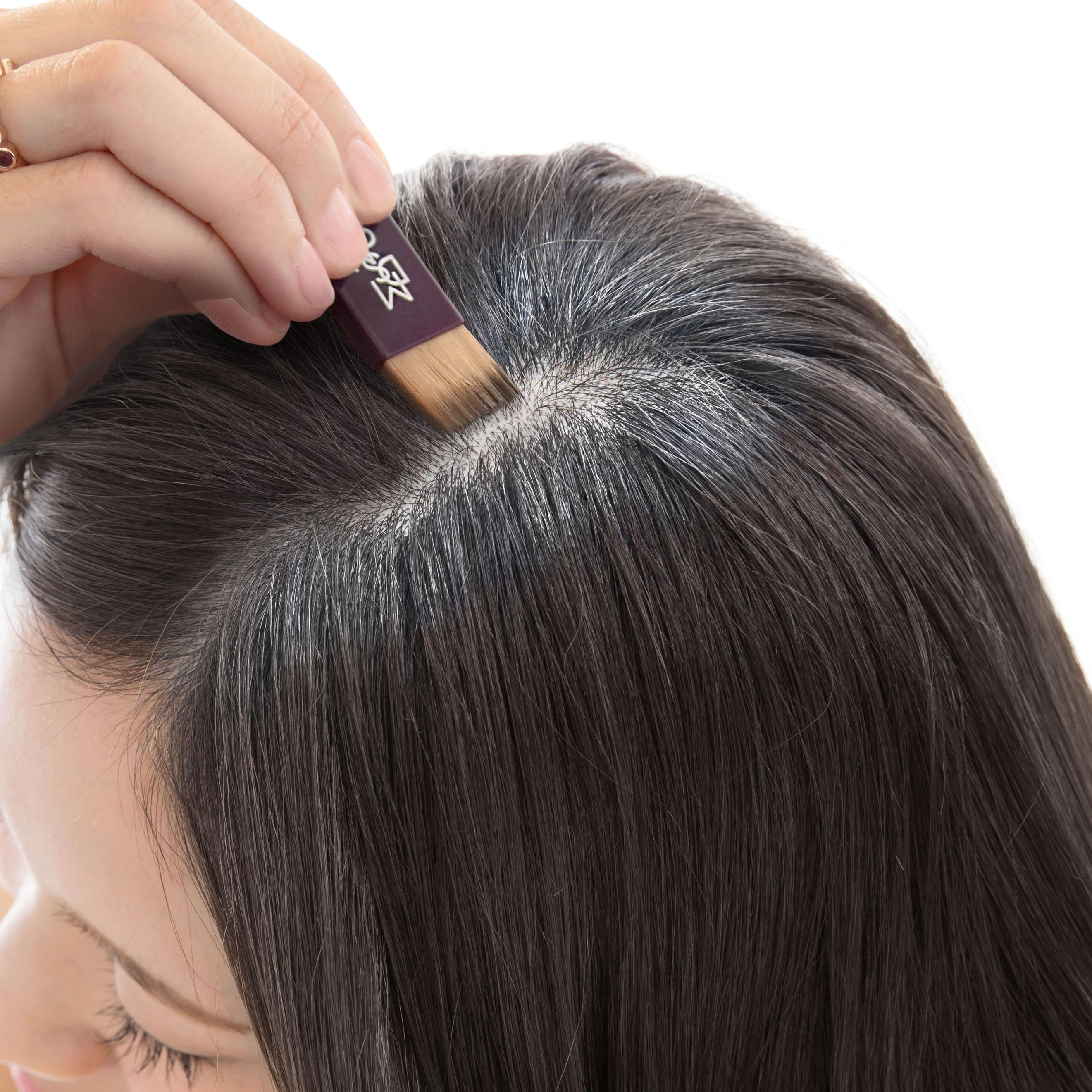 woman applying temporary hair color to her roots