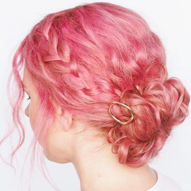 woman with bright pink hair in a bun