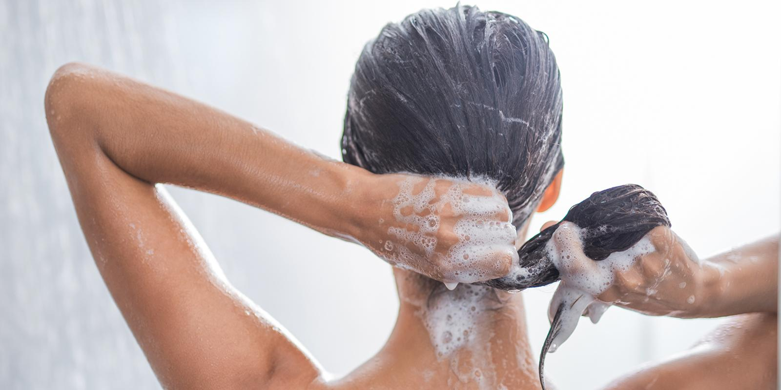 Woman with brunette hair Shampooing her hair