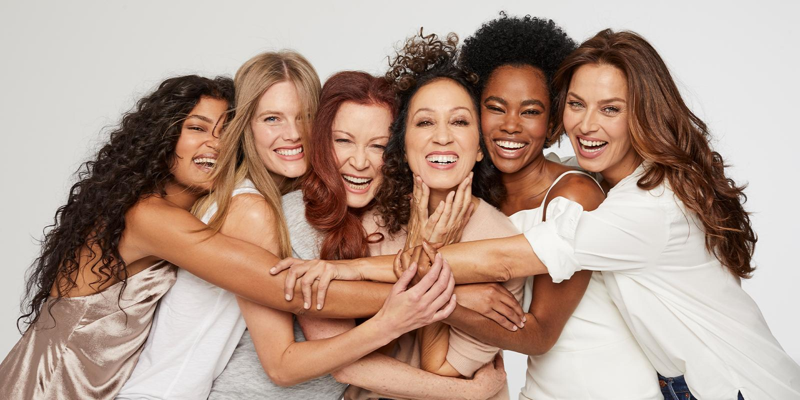Women with beautiful hair hugging and smiling