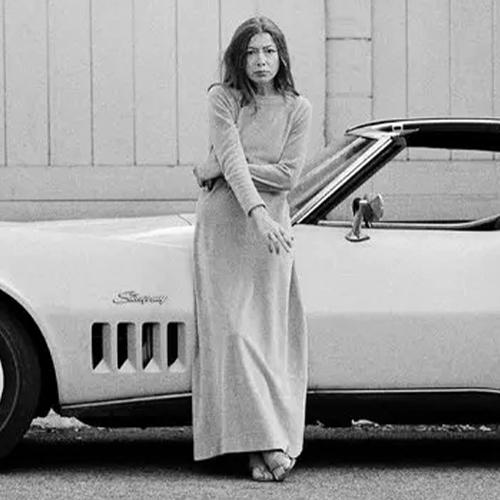 Joan Didion standing leaning on a car